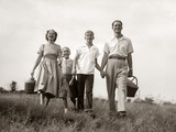 1950s Family Walking in Grassy Meadow Carrying Summer Picnic Basket and Thermos