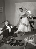 1950s-1960s Teen Couple Dressed for Prom  Girl Dancing to Music from a Record Player