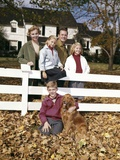 1960s Family with Dog at White Board Fence in Front of Colonial Style Suburban House
