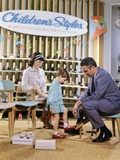 1960s-1970s Mother Watching Salesman Fit Shoes on Daughter in Shoe Section of Department Store
