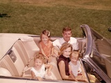 1960s-1970s Family Sitting in Open White Convertible Automobile