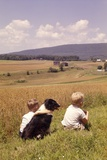 1960s Back of Two Boys with Black and White Dog Sitting Hillside Field Looking Down to Farm