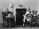 1940s Senior Couple Sitting in Living Room Reading Newspaper and Magazine Listening to Radio