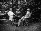 1900 Two Men Sitting Outside in Chairs Among Trees Smoking Cigars Talking Dog Laying at their Feet