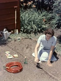 1950s Woman Kneeling in Garden Planting Seeds in Soil