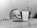 1950s Toddler Reaching Up to Table to Grab Milk Glass