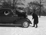 Woman Passenger Watching Man Motorist Try to Crank Start a Chevrolet Coupe Stalled in Snow