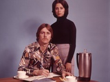 1970s Husband Wearing Loud Print Shirt Writing Family Budget and Wife Standing Behind Coffee Pot