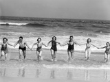 1930s Group 7 People Holding Hands Running Out of Surf onto Beach