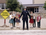 1960s Police Officer Holding Back Elementary School Children Waiting at Curb to Cross Street