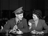 1940s Soldier in Army Uniform and Girlfriend Sitting at Soda Fountain Counter Eating Ice Cream