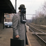 1950s Man Wearing Gas Mask Hat at Commuter Train Station Holding Briefcase Newspaper