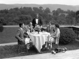 1920s-1930s Country Club Scene with Two Couples with Golf Clubs Having Lunch Outdoors