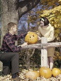 1960s Young Couple Man Woman in Autumn Woods Carving Halloween Jack-O-Lantern Pumpkin