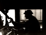 1920s-1940s Silhouette Train Engineer at Controls in Locomotive Cab of Railroad Steam Engine