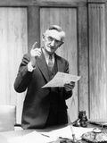 1930s Elderly Man in Office Standing Behind Desk Gesturing with Raised Finger