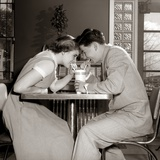 1950s-1960s Laughing Teenage Boy and Girl Sharing Drink Together with Two Straws in Soda Shop