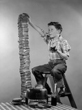 1950s Boy Eating Jelly Toast Sitting on Ladder Stacking Up Tall Pile of Toast from Toaster