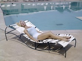 1960S Elegant Tall Woman in Bathing Suit Reclining on a Lounge Chair by Swimming Pool
