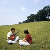 1970s African-American Couple Man Woman Sitting on Grassy Hill Man Playing Acoustic Guitar