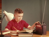1960s Red Hair Boy Sitting at Deslistening to Portable Radio While Studying Homework