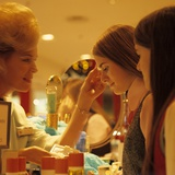 1970s Teen Girls at Make Up Counter in Store Having Eye Shadow Applied Tested
