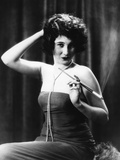 1920s Woman Wearing Strapless Gown String Pearls Holding Cigarette Holder Hand on Back of Head