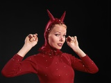 1960s Woman Red Devil Costume with Horns Arms Up in Air Looking Seductively at Camera