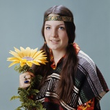1960s-1970s Teenage Girl with Pigtails Wearing Headband and Serape Holding Sunflower