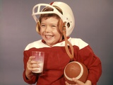 1950s-1960s Boy Drinking Milk Wearing Football Helmet Red Jersey Holding Ball