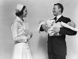 1930s-1940s Woman Nurse Talking with Man Proud New Father Holding Newborn Twin Babies