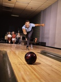 1960s Man Throwing Bowling Ball Down Alley as Family Watches in Background Fun Dad Father