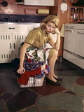 1960s Weary Dejected Woman Housewife Homemaker Sitting on Full Laundry Basket in Kitchen