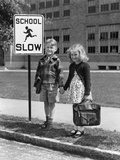 1930s-1940s Boy Girl Holding Hands Next to School Slow Sign