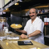 Portrait Man Working Behind Counter in Diner Holding Pie