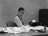 1930s-1940s Busy Man in Shirt Sleeves Behind Office Desk Working at Typewriter Smoking Cigarette