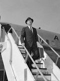 1960s Businessman Deplaning from Airplane Wearing Hat and Carrying Overcoat and Briefcase
