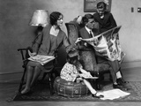 1920s Family of Four Mother Father Son Daughter in Living Room Reading Newspaper Together