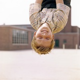 Red Haired Boy Hanging Upside Down in Elementary School Yard