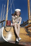 1940s Smiling Woman Wearing Nautical Sailor Outfit and Hat Sitting on Edge of Boat