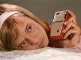 1950s-1960s Teenage Girl Holding Red Silver Small Transistor Radio to Her Ear Listening