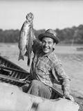 1940s-1950s Happy Man Fishing from a Rowboat Holding Up Fish Just Caught with Pride