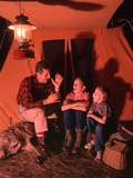1960s-1970s Grandfather Telling Scary Story to Boys by Tent at Night Campsite in Shadows