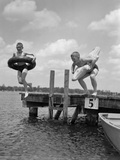 1940s-1950s Two Boys Wearing Inflatable Inner Tubes About to Jump in Lake Off Pier