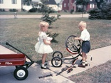 1950s Little Girl Sister Holding Doll Watching Little Boy Brother Repair Tricycle