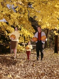 1960s Family Trio Father Mother Daughter Walking in Autumn Woods Carrying Pumpkins