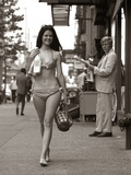 1970s Man Ogling Sexy Young Woman Walking Down City Street Wearing Only a Bikini
