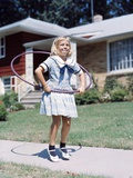 1950s-1960s Young Girl Playing with Hula Hoop Outside on Suburban Sidewalk in Sailor Style Dress