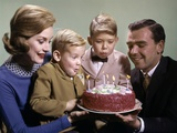 1960s Mother and Father Holding Birthday Cake and Sons Blowing Out Candles