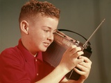 1960s Young Red Hair Pre-Teen Boy Listening to Portable Transistor Radio Held Up to Ear